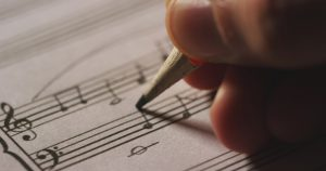 Composing a film score by hand on sheet music